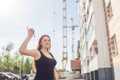 Bella donna sorridente le che mostra le nuove chiavi domestiche contro il contesto di una casa in costruzione Fotografia Stock