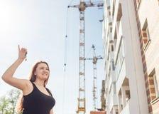 Bella donna sorridente le che mostra le nuove chiavi domestiche contro il contesto di una casa in costruzione Immagine Stock Libera da Diritti