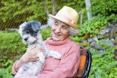 Bella donna sorridente senior con il cappello di paglia che abbraccia il suo cane nella montagna Immagini Stock