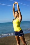 Bella donna sportiva che allunga e che si rilassa con la musica sulla spiaggia Fotografia Stock