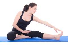 Bella donna sportiva che allunga gamba sul pavimento isolato su w immagini stock