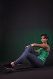 Bella donna sportiva che fa esercizio su un fondo scuro con la lampadina verde Fotografie Stock