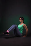 Bella donna sportiva che fa esercizio su un fondo scuro con la lampadina verde Fotografia Stock Libera da Diritti