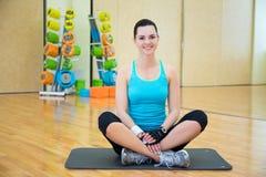 Bella donna sportiva che si rilassa dopo la formazione nella palestra fotografie stock