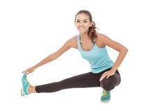 Bella donna sportiva che sorride mentre facendo allungamento delle gambe Fotografia Stock Libera da Diritti