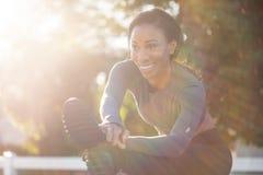 Bella donna sportiva con un sorriso affascinante che allunga le sue gambe Immagini Stock