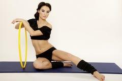 Bella donna sportiva nell'ente esile del vestito nero con il hula-hoop immagini stock libere da diritti