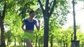 Bella donna sportiva sorridente che pareggia nel parco stock footage