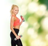 Bella donna sportiva sorridente con le teste di legno Immagini Stock