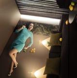 Bella donna straordinaria che si trova e che si rilassa sulla parete nella stanza capovolta con i limoni Immagine Stock
