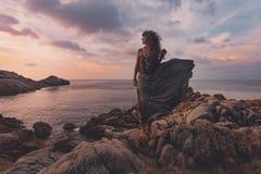 Bella donna sulla cima della roccia al tramonto sopra il backgr del mare Immagine Stock Libera da Diritti