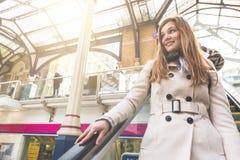 Bella donna sulla scala mobile alla stazione ferroviaria Immagine Stock