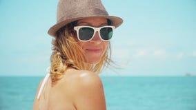 Bella donna sulla spiaggia che osserva indietro il movimento lento sorridente della macchina fotografica stock footage