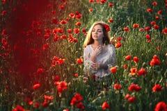 Bella donna in un campo del papavero Immagini Stock