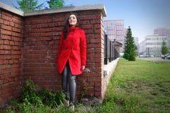 Bella donna in un cappotto rosso su un muro di mattoni nella città immagini stock libere da diritti