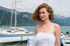 Bella donna in un vestito bianco che sta sul pilastro Fotografie Stock Libere da Diritti