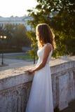 Bella donna in un vestito bianco vicino a calcestruzzo antico bianco Fotografia Stock