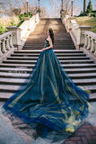 Bella donna in un vestito blu lussuoso con un treno lungo Immagini Stock