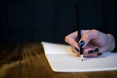 Bella donna in un vestito nero con un taccuino aperto con la penna e la matita, studio isolato su fondo nero Fotografie Stock Libere da Diritti