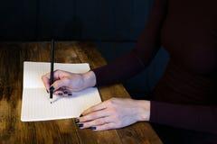 Bella donna in un vestito nero con un taccuino aperto con la penna e la matita, studio isolato su fondo nero Immagini Stock Libere da Diritti
