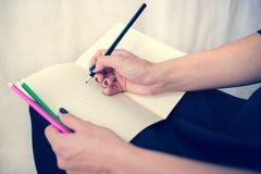Bella donna in un vestito nero con un taccuino aperto con la penna e la matita, studio isolato su fondo bianco Fotografie Stock