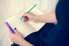 Bella donna in un vestito nero con un taccuino aperto con la penna e la matita, studio isolato su fondo bianco Fotografia Stock Libera da Diritti