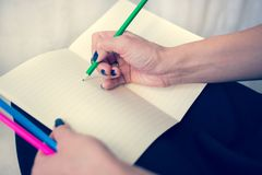Bella donna in un vestito nero con un taccuino aperto con la penna e la matita, studio isolato su fondo bianco Immagine Stock Libera da Diritti