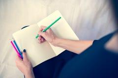 Bella donna in un vestito nero con un taccuino aperto con la penna e la matita, studio isolato su fondo bianco Fotografie Stock Libere da Diritti