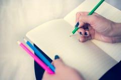 Bella donna in un vestito nero con un taccuino aperto con la penna e la matita, studio isolato su fondo bianco Immagine Stock