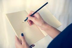 Bella donna in un vestito nero con un taccuino aperto con la penna e la matita, studio isolato su fondo bianco Immagini Stock
