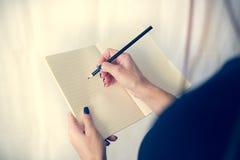 Bella donna in un vestito nero con un taccuino aperto con la penna e la matita, studio isolato su fondo bianco Immagini Stock Libere da Diritti
