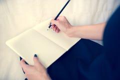 Bella donna in un vestito nero con un taccuino aperto con la penna e la matita, studio su fondo bianco Immagine Stock