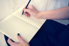 Bella donna in un vestito nero con un taccuino aperto con la penna e la matita, studio su fondo bianco Immagini Stock