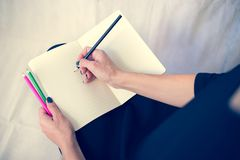 Bella donna in un vestito nero con un taccuino aperto con la penna e la matita, studio su fondo bianco Fotografie Stock Libere da Diritti