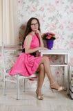 Bella donna in un vestito rosa su una sedia Fotografia Stock