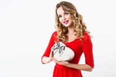 Bella donna in un vestito rosso con un contenitore di regalo sotto forma di un cuore Immagine Stock