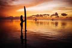 Bella donna in una muta subacquea per praticare il surfing di nuoto nell'Oceano Indiano fotografia stock libera da diritti