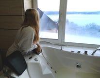 Bella donna in una vasca calda Jacuzzi nell'hotel, vista panoramica dalla finestra nel bagno fotografie stock libere da diritti