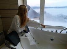 Bella donna in una vasca calda Jacuzzi nell'hotel, vista panoramica dalla finestra nel bagno immagini stock libere da diritti