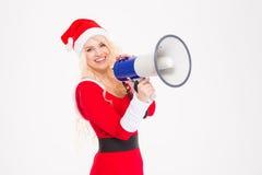 Bella donna in vestiti e cappello del Babbo Natale con il megafono Fotografie Stock