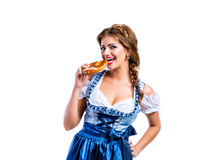 Bella donna in vestito bavarese tradizionale che tiene una ciambellina salata Immagini Stock