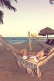 Bella donna in vestito bianco in amaca accanto all'oceano, retro Immagine Stock Libera da Diritti