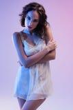 Bella donna in vestito bianco e nella luce blu su fondo blu Immagine Stock