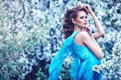 Bella donna in vestito blu fra di melo del fiore, modo Fotografie Stock