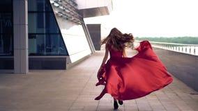 Bella donna in vestito d'ondeggiamento rosso video d archivio