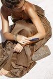 Bella donna in vestito elegante che si siede sulla sabbia alla spiaggia Fotografie Stock Libere da Diritti