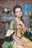 Bella donna in vestito medievale sulla sedia fotografia stock libera da diritti