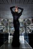 Bella donna in vestito nero lungo - rispecchi la stanza immagine stock libera da diritti