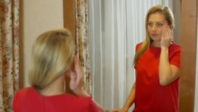 Bella donna in vestito rosso che considera riflessione in specchio video d archivio