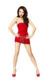Bella donna in vestito rosso che si leva in piedi provocatorio fotografia stock